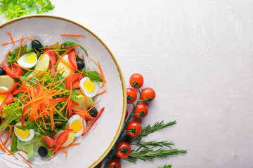 Vegetable salad with chicken eggs. On a wooden background. Top view. Free space for your text.
