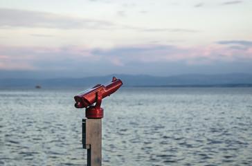 Ein Fernrohr am Ufer des Bodensees bei Überlingen mit Blick auf das Wasser und die Berge