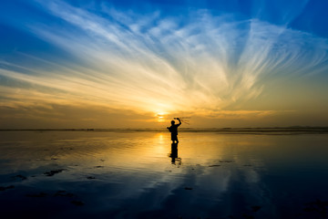 Minimal Silhouette of happy tourist with poles in hand above head on the beach with sunrise sky.