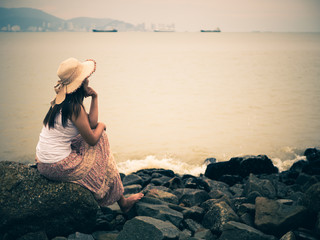 Retro lonely and depressed woman sitting in front of the sea in a deserted beach on an Autumn day.