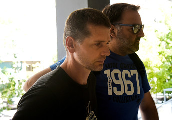 Alexander Vinnik, a Russian man suspected of running a money laundering operation, is escorted by a plain-clothes police officer to a court in Thessaloniki