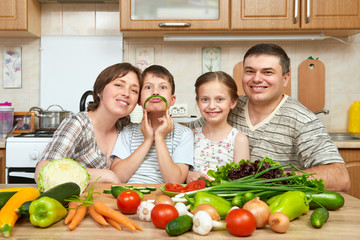 family portrait in kitchen interior at home, fresh fruits and vegetables, healthy food concept, woman, man and children cooking and having fun