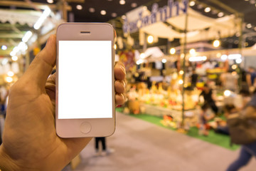 Holding mobile phone with de-focused shopping exhibition background, blank screen for text