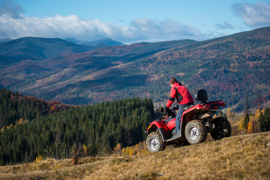 Man riding down on an ATV the hilly road on a background of mountains, forest and blue sky. The concept of an active holiday in the mountains