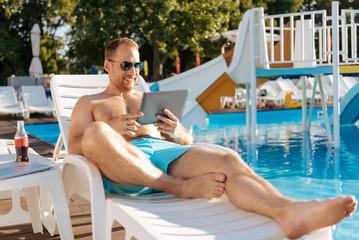 Pleasant man watching a film on tablet near pool