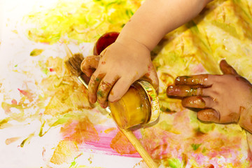 Painted hands smudging colors on messy table