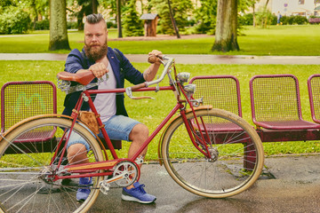 Redhead bearded male on a retro bicycle in a park.