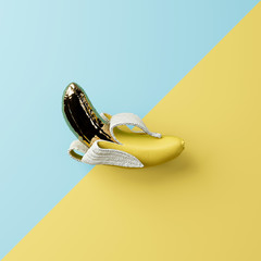gold peeled banana isolate on blue and yellow pastel background for minimal tropical fruit concept. 3d illustration
