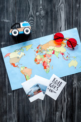 tourist outfit with map for trip with kids dark wooden background top view