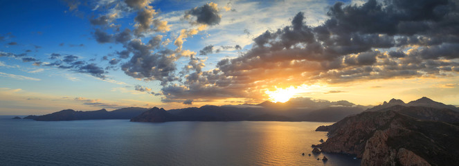 Panorama of a summer sunrise over the sea and a beautiful mountain landscape. At Capu Rossu, on the island of Corsica, France.