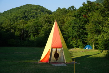 Yellow-orange wigwam on the grass near the mountain forest