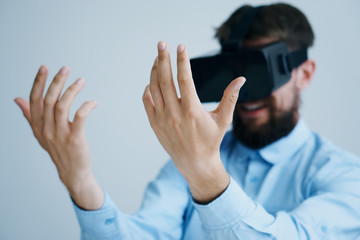 1226015 A man with a beard on a light background in glasses of virtual reality