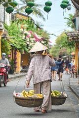Unrecognizable traditional banana fruit vendor from behind in Hoi An, Vietnam.