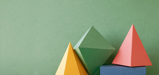 Colorful abstract geometric background with three-dimensional solid figures. Pyramid prism rectangular cube arranged on green paper. Yellow blue pink malachite colored geometrical shapes. Soft focus