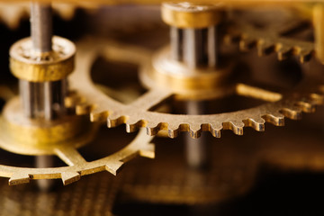 Industrial machinery bronze cog transmission macro view. Aged metal gear wheel teeth mechanism, shallow depth field selective focus.
