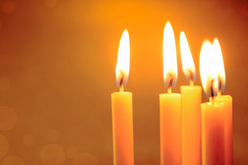 Group of still life  golden candle light with reflection on soft red blurred  background. Abstract background for pray or meditation caption and hope concept