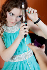 Beautiful teenage girl curling long hair with curler