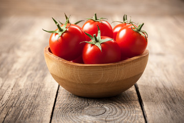 Fresh tomatoes in a wooden bowl on wooden table