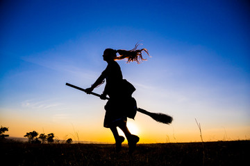 Silhouette of young witch flying on the broomstick at sky
