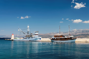 Two ships in the harbor of a small town at a daytime - Croatia, island Brac