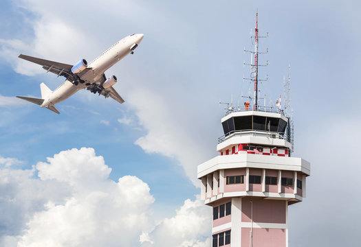Air traffic control tower in international airport with passenger airplane jet taking off on blue sky