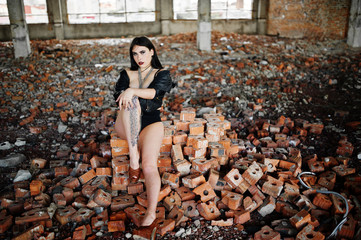 Brunette plus size sexy woman, wear at black leather jacket, lace panties, bra and high heels with chain at hands, siting on brick at abadoned place. BDSM theme.