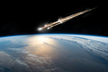 Wall Mural - A meteor streaks towards a collision with Earth as it breaks up over the ocean.  Clouds cover an ocean area of the planet.