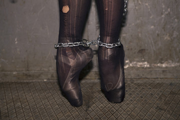 Chained woman legs with ballet shoes