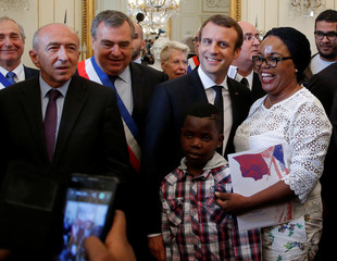 French Interior Minister Gerard Collomb, left, and French President Emmanuel Macron, center, pose with Aurelie Dion, as she becomes a French citizen during a citizenship ceremony in Orleans