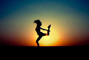 teen girl jumping at sunset. silhouette photo