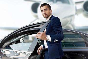 Businessman opens the car door