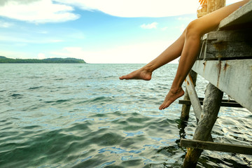 leg a woman sit on walkway wood for relax in holiday with sunset light at sea