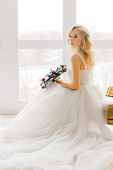 Young beautiful bride sitting on couch in white expensive wedding dress and posing for camera. Preparation for marriage.  Makeup and hairstyle.  Skinny blonde with curly hair.  Festive gala morning.