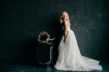 Pinup style portrait of beautiful elegant bride in expensive italian stylish wedding dress showing artisctic emotions on black texture wall background. Cute girl with slender posture and slim body.