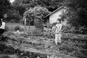 Young girl in garden, holding garden tool, black and white
