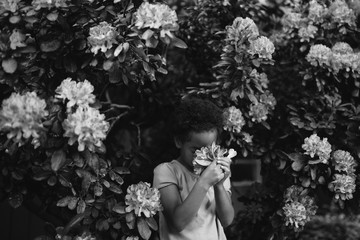 Young girl in garden, smelling flowers, black and white
