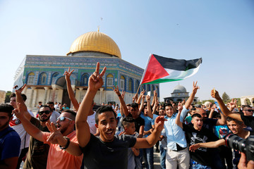The Dome of the Rock is seen in the background as a man waves a Palestinian flag upon entering the compound known to Muslims as Noble Sanctuary and to Jews as Temple Mount, after Israel removed all security measures it had installed at the compound, in Jer