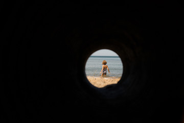 Looking at girl in lake through hole