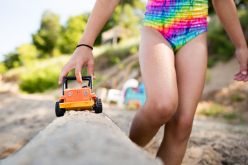 Girl pushing play truck on the beach