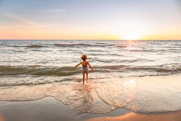 Girl entering the water, Lake Michigan, USA