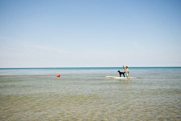 Man and his dog paddle boarding