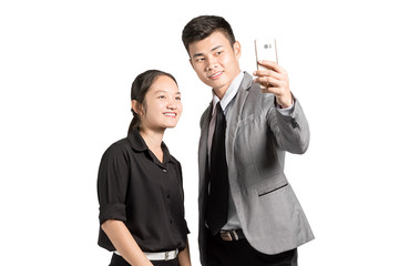 portrait of asian business woman and business man smiling and making a selfie with smart phone. Isolated on white background with copy space and clipping path