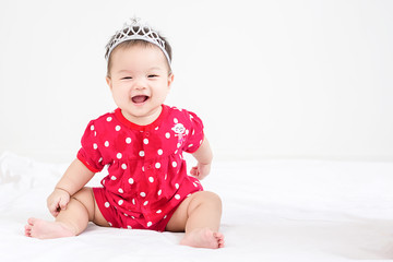 Portrait of a little adorable infant baby girl sitting on the bed and smiling to camera with copyspace