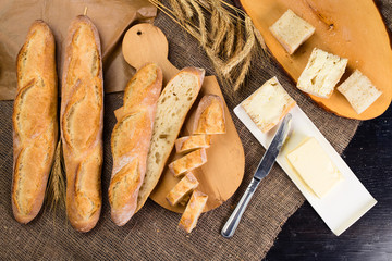 still life with French fresh bread baguettes with poolish on a wooden cutting board, butter and wheat. Shallow dof, flat lay