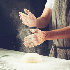 man baker sprinkled flour on roll dough on a wooden board. Process of preparing pizza. Cooking time, cooking concept, selective focus, toned image
