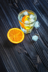 Cocktail with ice cubes and orange slice in a glass on dark wooden table