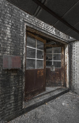 Rusted doors and bricks on the exterior of an abandoned factory