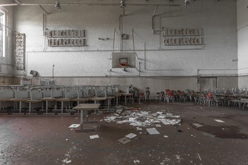 Gymnasium with stacked desks in abandoned high school