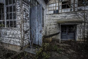Exterior of an abandoned factory with open door