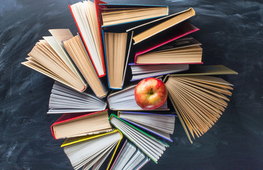 Some books and red apple on the desk over the blackboard